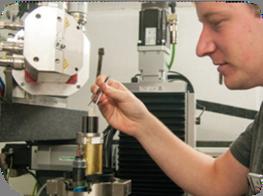 Студент Jeroen Van Stappen загружает образец камня в оснастку Deben CT5000, установленную на один из сканеров в центре технологий неразрушающего контроля на базе Гентского университета